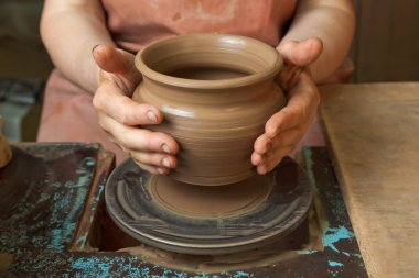 Potter creates a pitcher on a pottery wheel