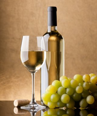 A bottle of white wine, glass and grapes