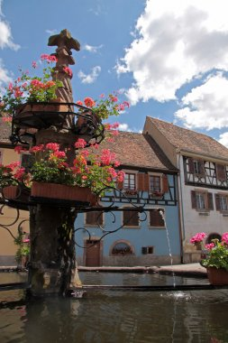 Village fountain with with blue half-timbered house