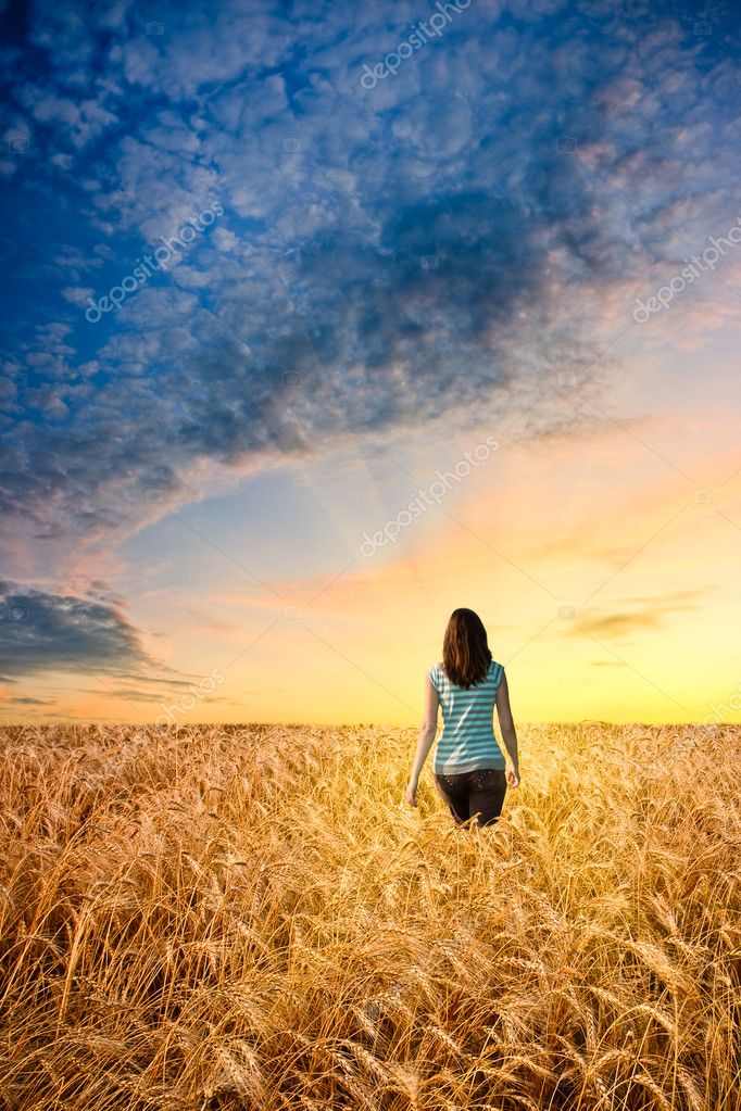 Woman in wheat field walking to sunset