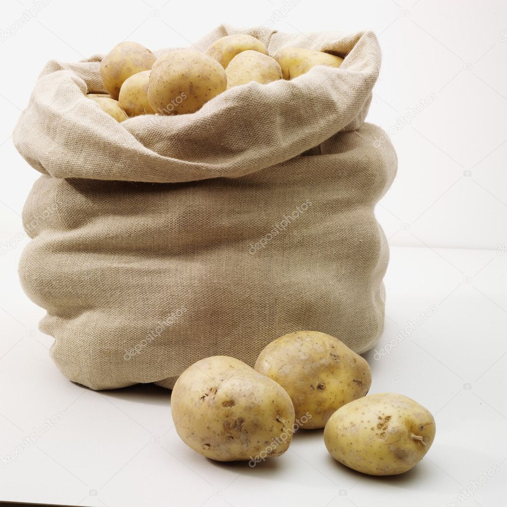 Overflowing bag of potatoes on whit