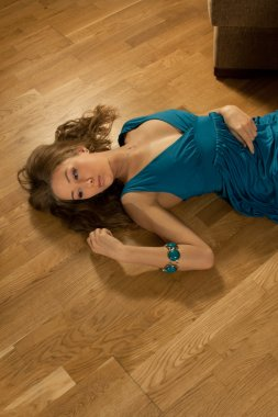Young woman in a dark blue evening dress lays on a parquet