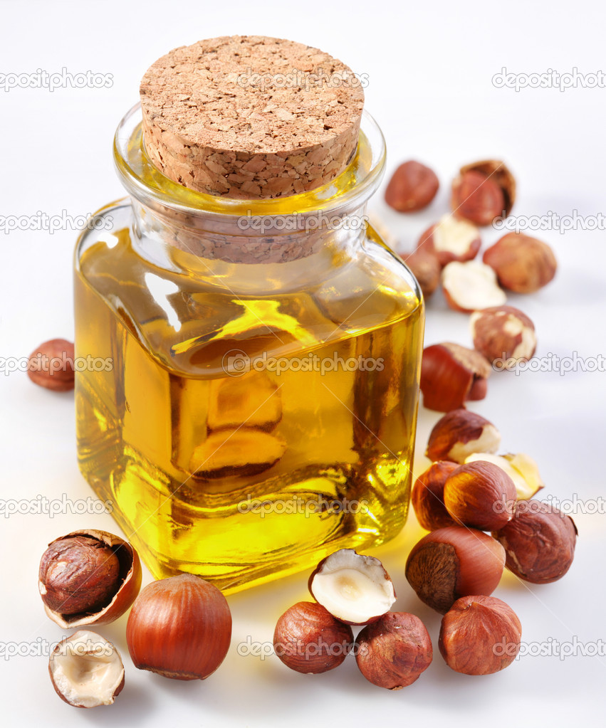 Filbert oil with nuts on a white background