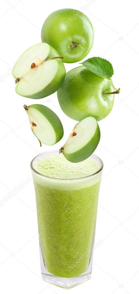 Slices of apple falling into a glass of fresh juice