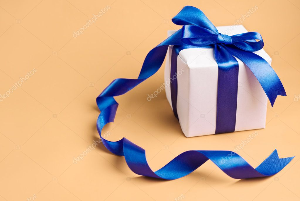 White gift with blue ribbon on a biege background