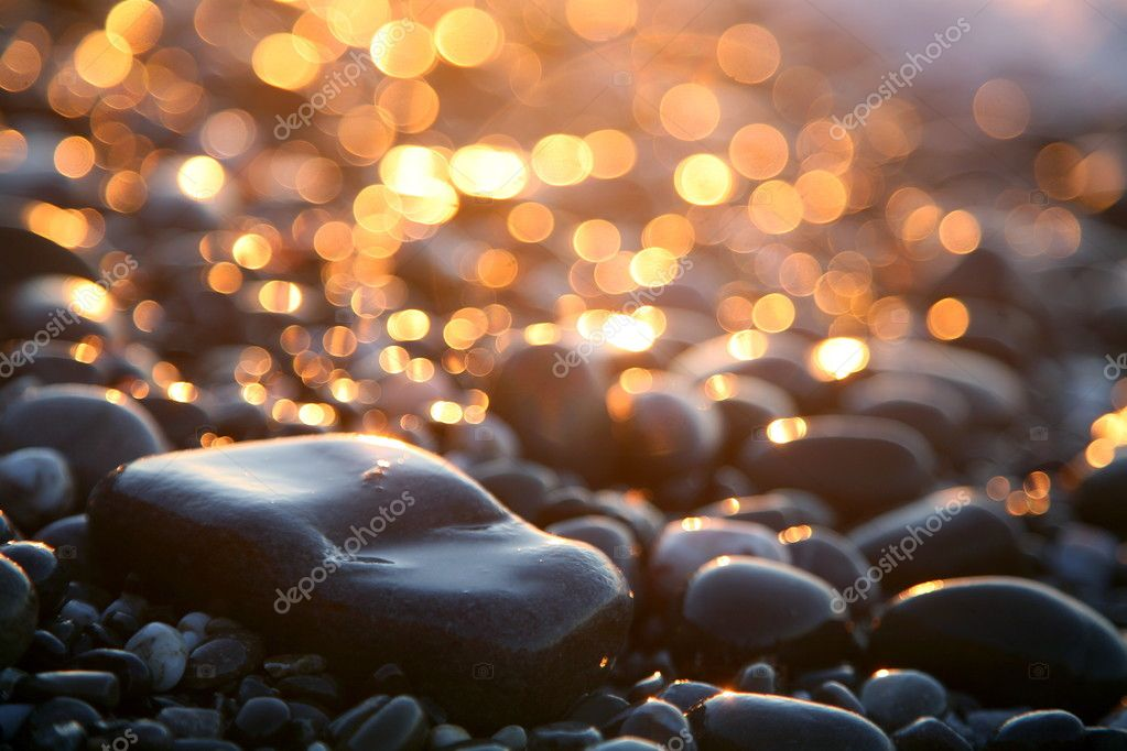 Background with sea stones and orange blurred circles.