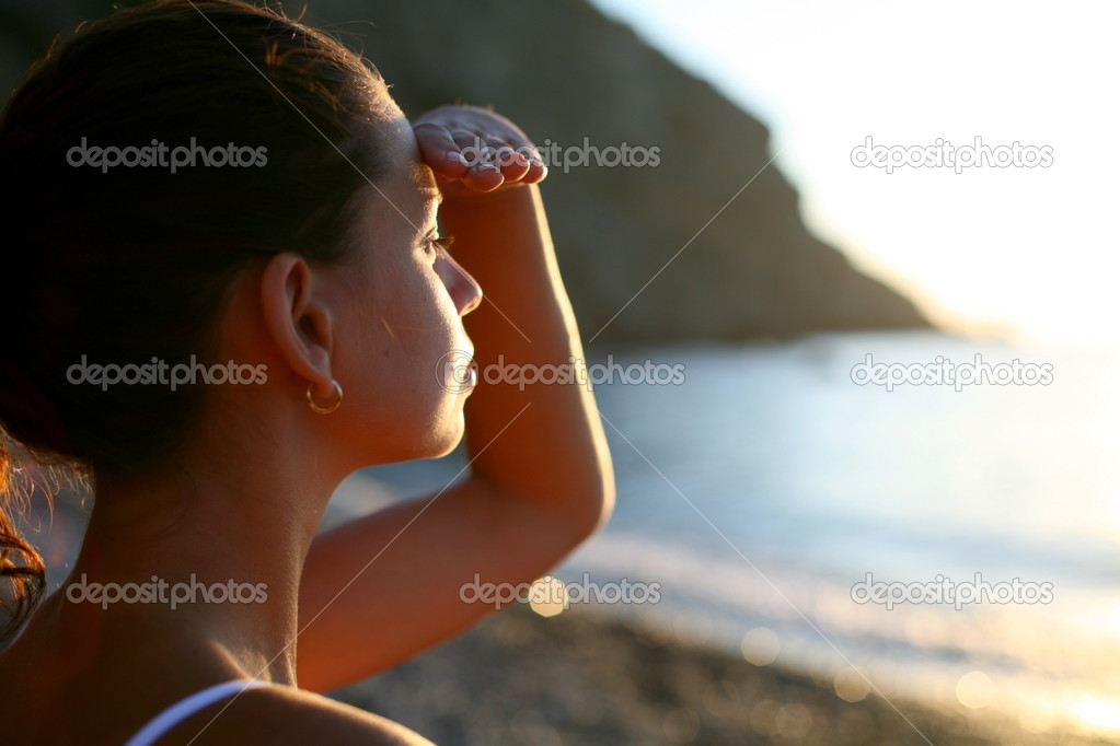 Beautiful brunette is looking into the sea