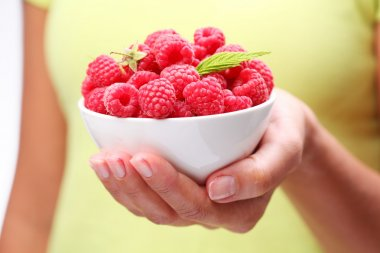 Crockery with raspberries in woman hand.