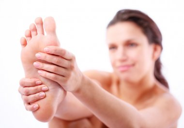 Young woman massages her foot. On a white background.