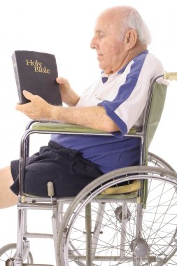 Old man in wheelchair reading a bible