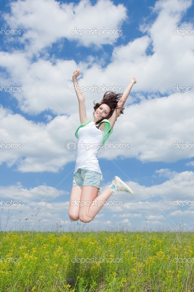 Jumping happy young brunette women on summer field