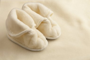Pair of warm children slippers on a woolen texture