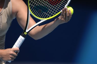 woman with tennis ball and raquet