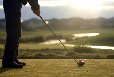 golfer tees off at putting green