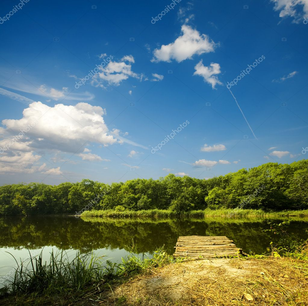 Wooden pier on summer river and forest on the backside