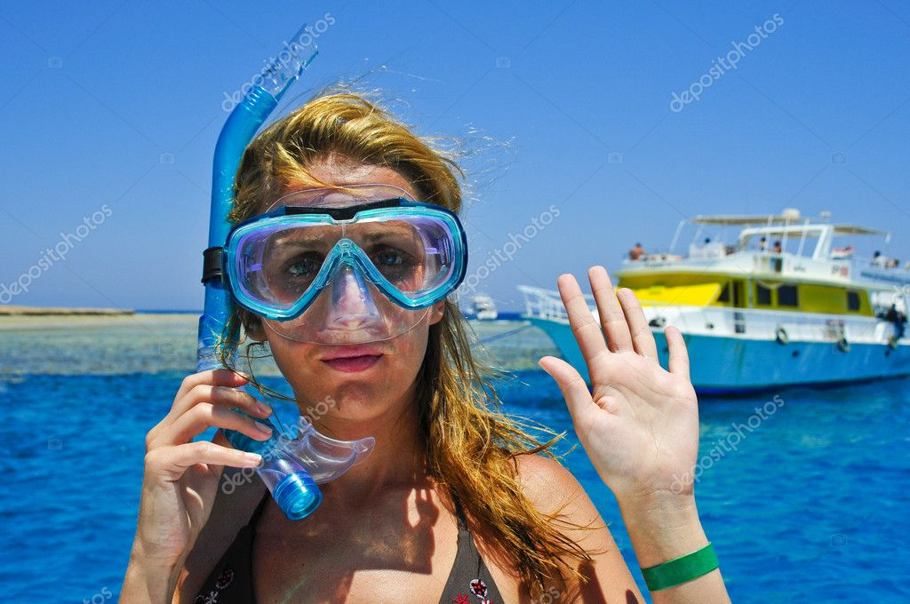 The beautiful girl is snorkeling with a mask in a red sea