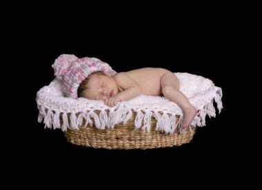 Newborn baby sleeping in basket with hat