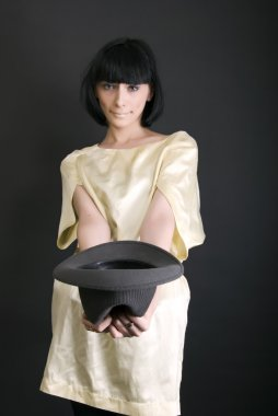 Young brunette holding a hat
