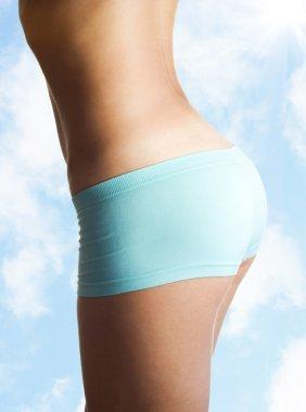 Beautiful tanned woman body in bikini over the sky