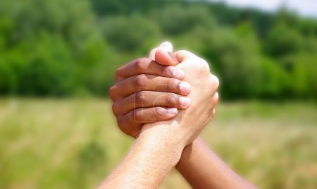 Photo pour Main dans la main sur un fond vert - image libre de droit