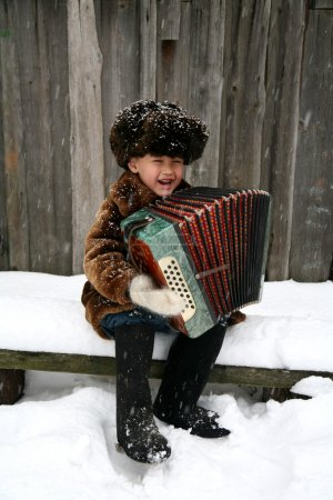 Photo pour Garçon avec accordéon sous la neige - image libre de droit