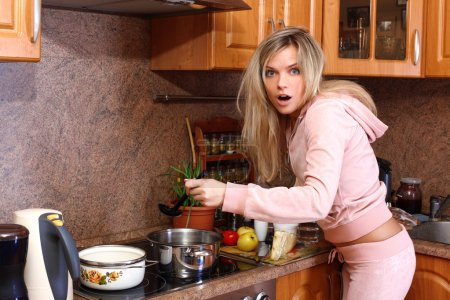 Funny surprised woman cooking dinner in the kitchen