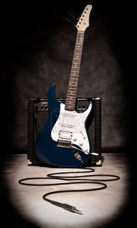 Photo for Electric guitar and amplifier on dark background, sepia toned - Royalty Free Image