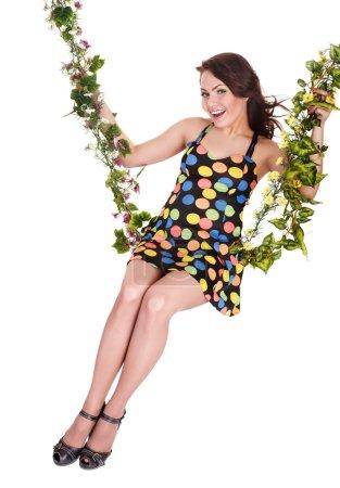 Beautiful girl swinging on flower swing.