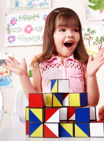 Photo pour Enfant avec bloc de bois et construction dans la salle de jeux. Préscolaire . - image libre de droit