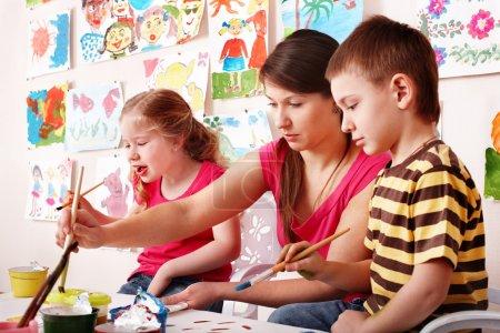 Foto de Niño con el maestro dibuja pinturas en la sala de juegos. preescolar.. - Imagen libre de derechos