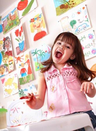 Little girl painting picture in preschool.