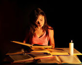 Girl reading book on table.