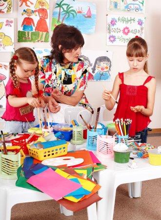 Foto de Niño con el maestro dibuja pinturas en sala de juegos. preescolar. - Imagen libre de derechos