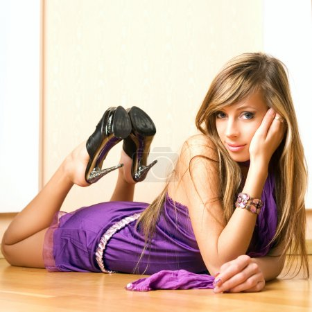 Photo for The sensual woman in a violet dress on the floor. - Royalty Free Image