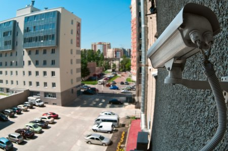 Optical camera on wall of building watching on parking