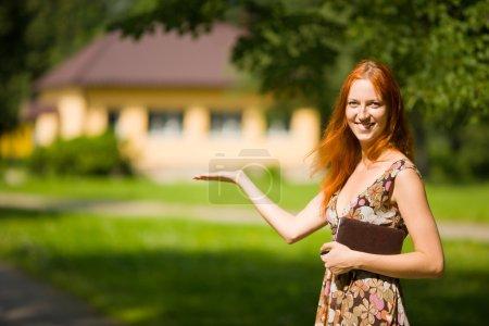 Photo pour Agence immobilière sourires près d'une maison neuve à vendre - image libre de droit