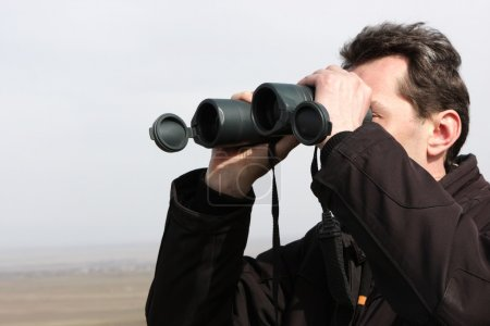 Man looks through binoculars