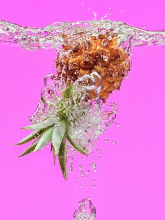 Small pineapple falling in water