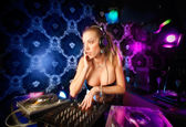 Sexy young blonde lady DJ playing music in night club