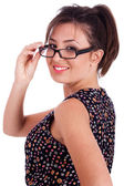 Young pretty woman in side pose looking at you over her glasses