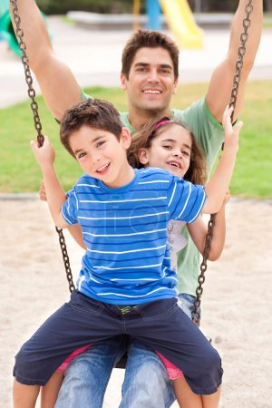 Father and children enjoying swing ride