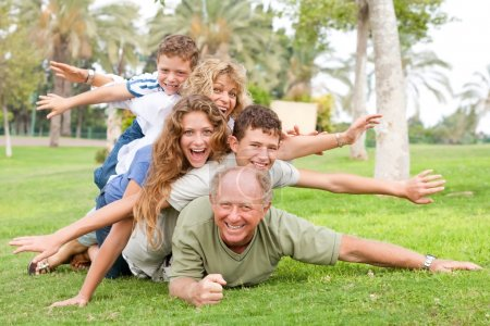 Photo for Portrait of family laying on each other with flying hands in a park - Royalty Free Image