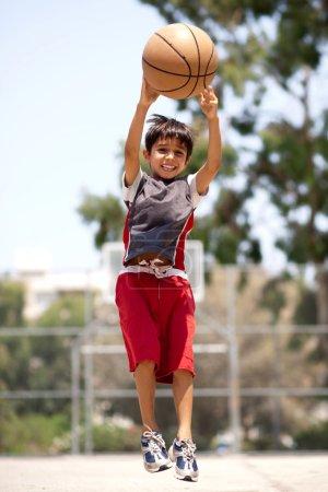 Photo pour Jeune joueur de basket-ball sautant haut dans les airs alors qu'il lance la balle - image libre de droit