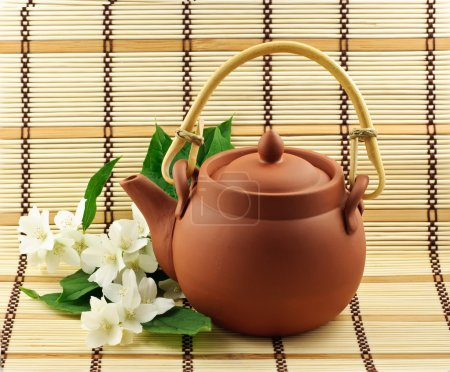 Foto de Tetera de arcilla para el té con flores de jazmín - Imagen libre de derechos