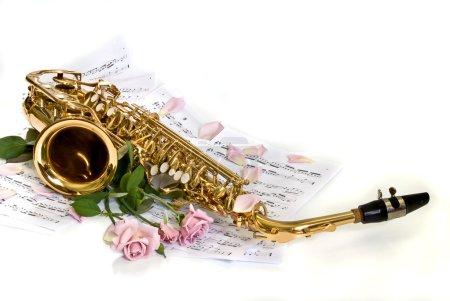 Photo pour Saxophone alto contre des notes de roses - image libre de droit