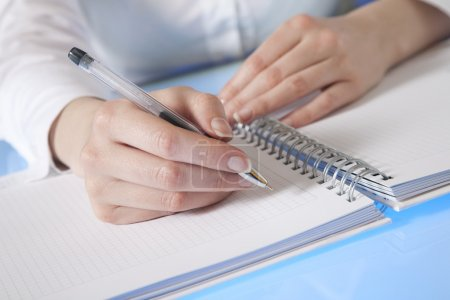 Photo for Woman's hand starting to make notes in a diary - Royalty Free Image