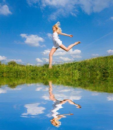 Photo pour Une femme heureuse court sur un champ - image libre de droit