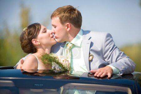 Photo pour Mariée et marié baisers sur mariage auto - image libre de droit