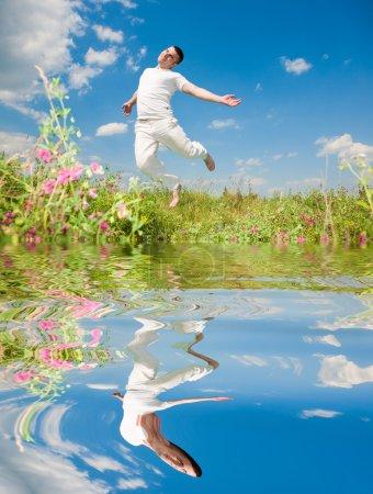 Photo pour Joyeux jeune homme - sautant. Reflété dans l'eau - image libre de droit