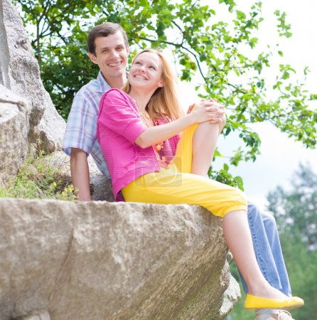 Casual happy couple sits on a rock